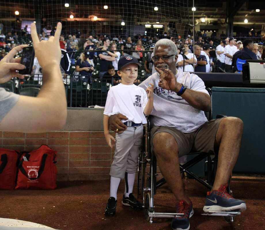 Earl Campbell poses for a photo with Xander Fiterman, 4, as his dad, D.J. takes a photo during a pre-game ceremony honoring New York Yankees relief pitcher Mariano Rivera. Photo: Karen Warren, Houston Chronicle