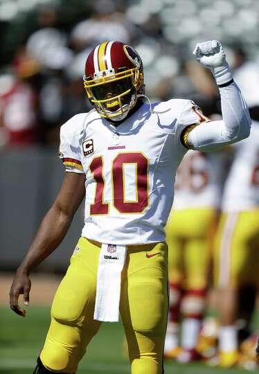 Washington Redskins quarterback Robert Griffin III (10) gestures as he warms up before an NFL footba