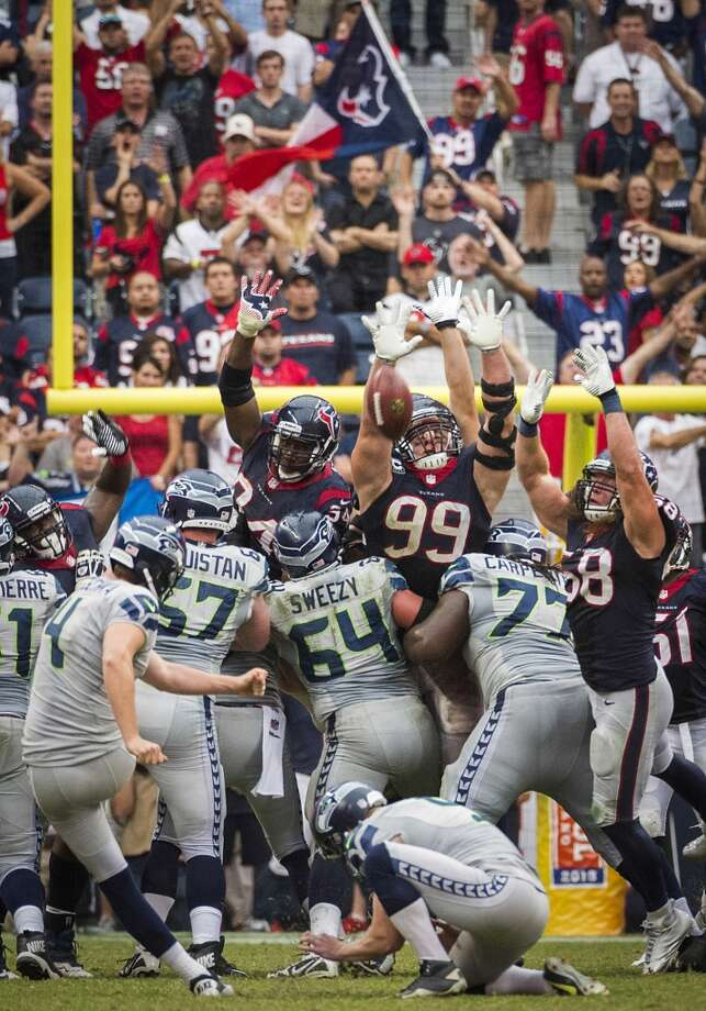 Seahawks kicker Steven Hauschka (4) kicks a 45-yard game-winning field goal over the outstretched hands of Texans defensive end Antonio Smith (94), defensive end J.J. Watt (99) and outside linebacker Brooks Reed (58) during overtime. Photo: Smiley N. Pool, Houston Chronicle
