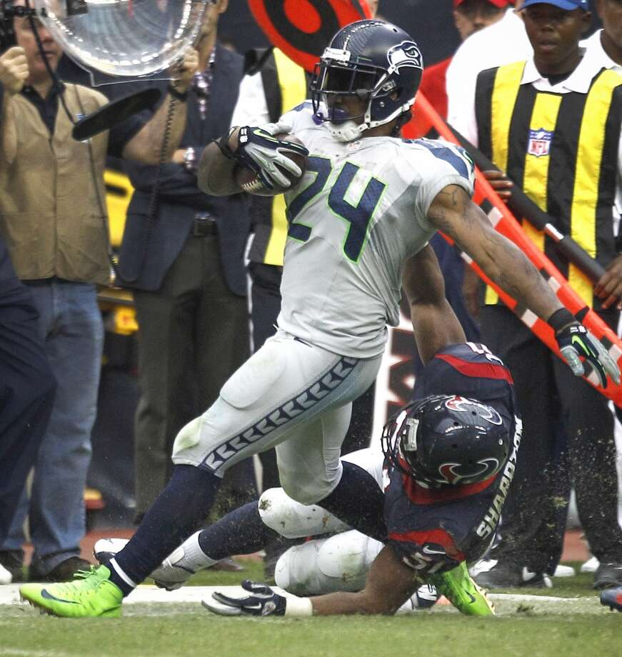 Seahawks running back Marshawn Lynch is tackled on the sidelines by Texans inside linebacker Darryl Sharpton in overtime. Shaprton was called for a horse collar penalty on the play. Photo: Brett Coomer, Houston Chronicle
