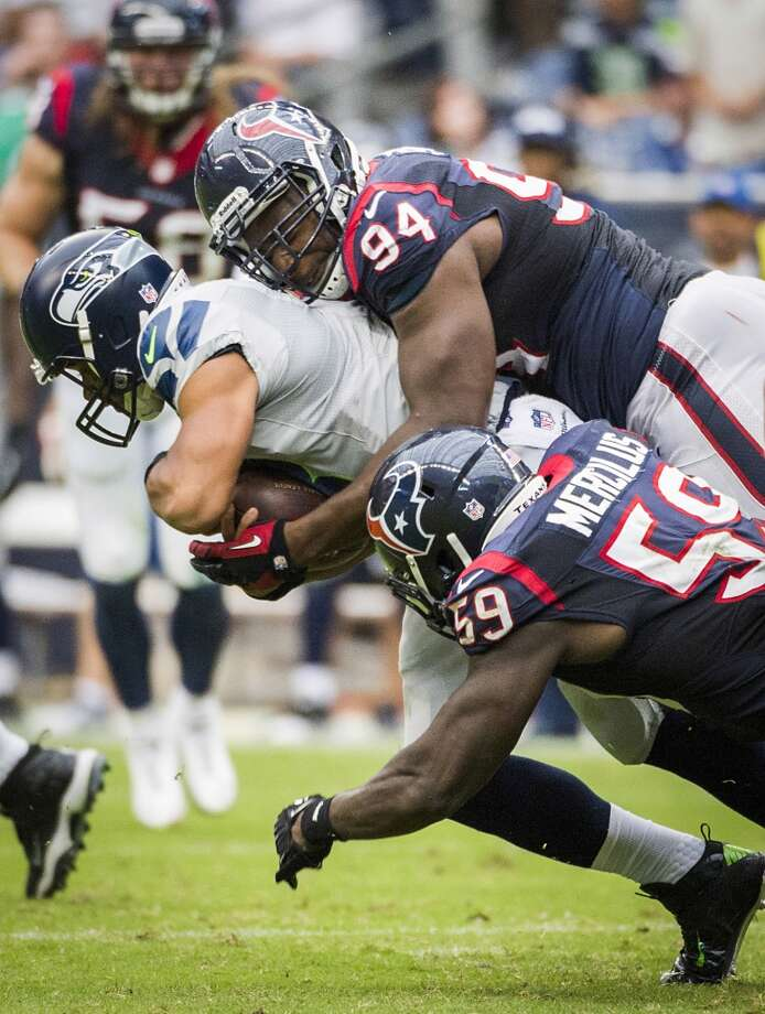 Texans defensive end Antonio Smith (94) and outside linebacker Whitney Mercilus (59) sack Seahawks quarterback Russell Wilson. Photo: Smiley N. Pool, Houston Chronicle