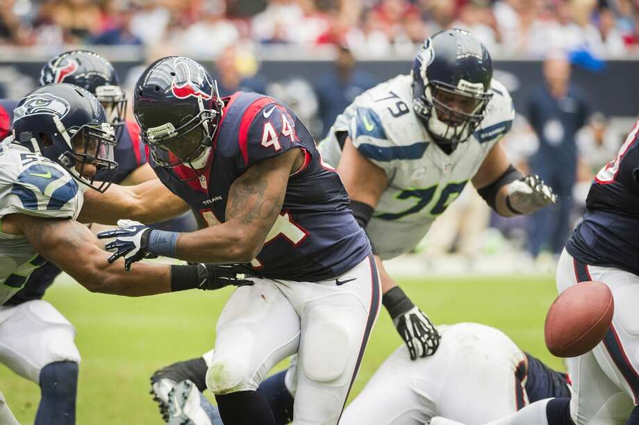 Texans running back Ben Tate fumbles as he is hit by Seahawks linebacker Malcolm Smith. Photo: Smiley N. Pool, Houston Chronicle