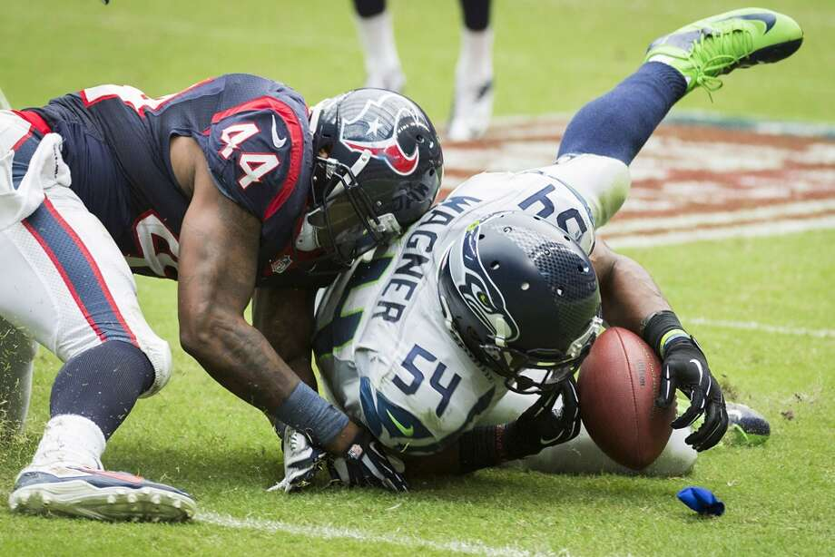 Seahawks linebacker Bobby Wagner recovers a fumble by Texans running back Ben Tate. Photo: Smiley N. Pool, Houston Chronicle