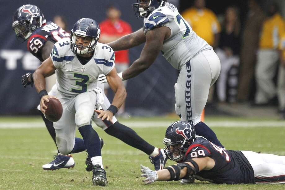 Seahawks quarterback Russell Wilson runs out of the grasp of Texans defensive end J.J. Watt. Photo: Brett Coomer, Houston Chronicle