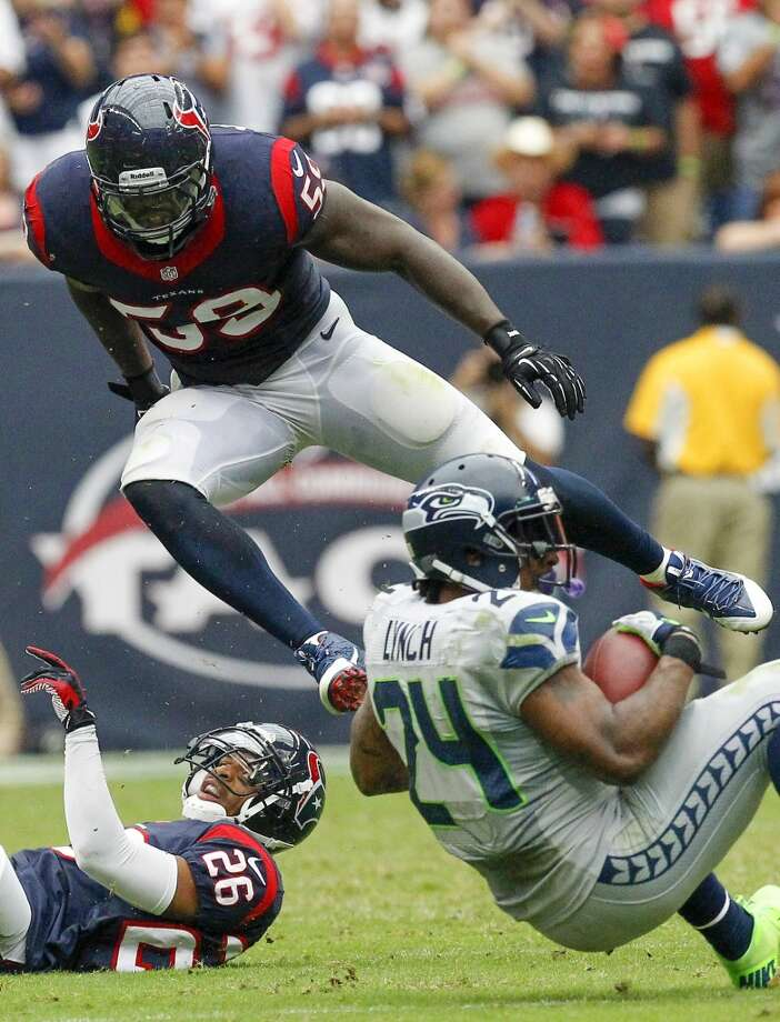 Texans defensive back Brandon Harris, left, watches as Texans outside linebacker Whitney Mercilus jumps over Seahawks running back Marshawn Lynch. Photo: Cody Duty, Houston Chronicle