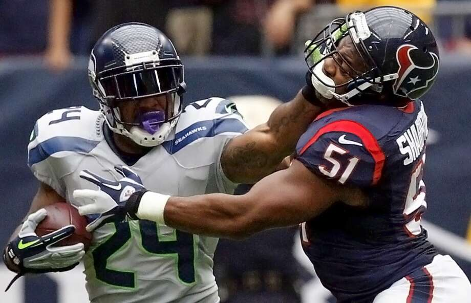 Seahawks running back Marshawn Lynch stiff arms Texans inside linebacker Darryl Sharpton. Photo: Cody Duty, Houston Chronicle
