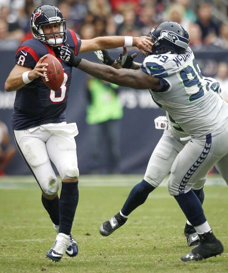 Texans quarterback Matt Schaub is forced out of the pocket by Seahawks defensive tackle Tony McDaniel. Photo: Brett Coomer, Houston Chronicle