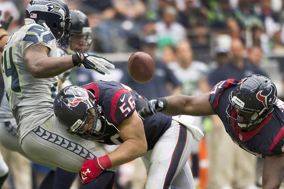 Seahawks running back Marshawn Lynch fumbles as he is hit by Texans inside linebacker Brian Cushing. Photo: Smiley N. Pool, Houston Chronicle