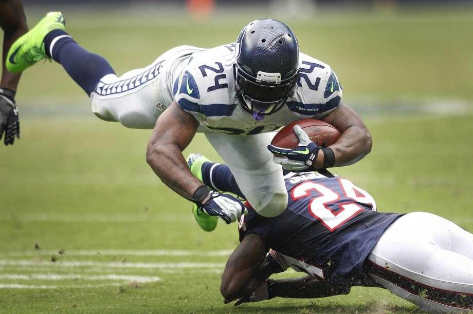 Seahawks running back Marshawn Lynch is tripped up by Texans cornerback Johnathan Joseph. Photo: Brett Coomer, Houston Chronicle