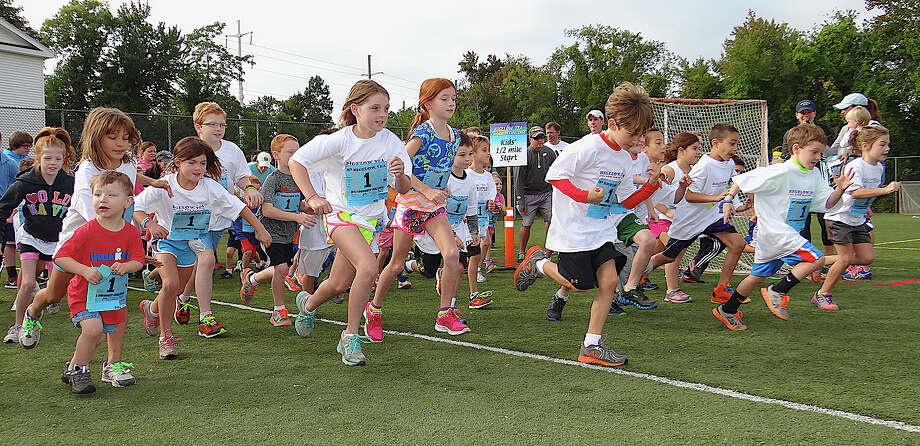 Younsters leap from the start line as the Half-Mile Kids Run gets underway Sunday at the 26th annual Bigelow Tea Community Challenge at the Wakeman Boys & Girls Club. Photo: Mike Lauterborn / Fairfield Citizen contributed