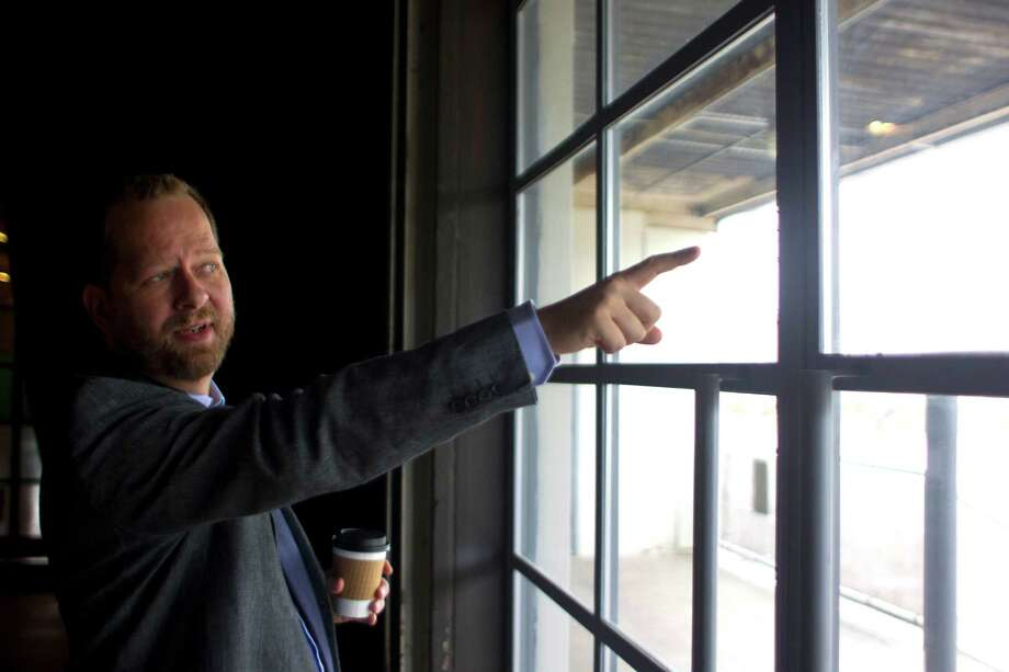 Chris Seay, pastor of Ecclesia Church points out of the former paper company building where he now leads his congregation talking about some if the history in the First Ward Friday, Sept. 27, 2013, in Houston. Photo: Johnny Hanson, Houston Chronicle / Houston Chronicle