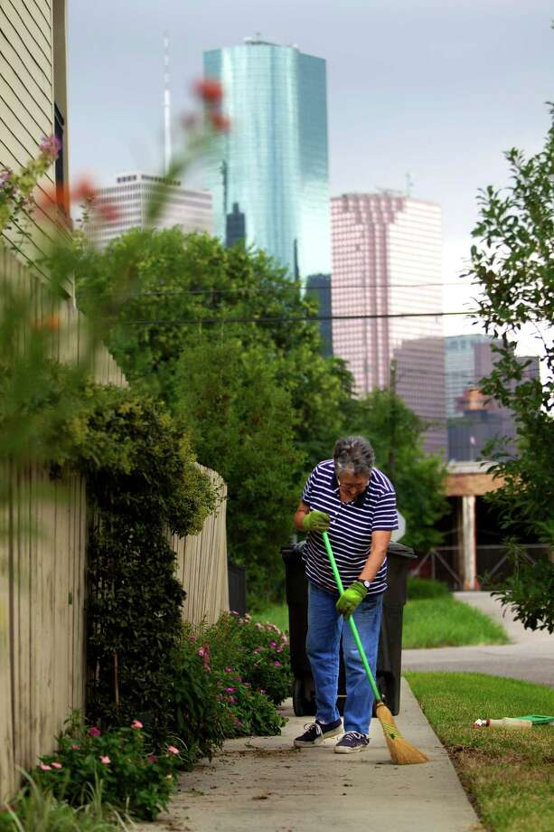 """Marjorie Fruge sweeps her sidewalk next to her town home in the First Ward the Friday, Sept. 27, 2013, in Houston.  Fruge said she likes the changes she's seen since she moved to the neighborhood in 2005. """"This was a dump,"""" Fruge said about the home across the street from her town house. """"I use to watch out of my kitchen window and watch drug deals. (The neighborhood) is changing fast."""" Photo: Johnny Hanson, Houston Chronicle / Houston Chronicle"""