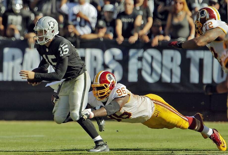 Matt Flynn is sacked by Washington's Barry Cofield in the fourth quarter, one of seven sacks that Flynn endured in the game Sunday. The Oakland Raiders played the Washington Redskins at O.co Coliseum in Oakland, Calif., on Sunday, September 29, 2013. Photo: Carlos Avila Gonzalez, The Chronicle