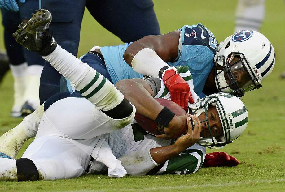 Tennessee Titans linebacker Zach Brown, top, sacks New York Jets quarterback Geno Smith, bottom, for an 11-yard loss in the fourth quarter of an NFL football game on Sunday, Sept. 29, 2013, in Nashville, Tenn. The Titans won 38-13. (AP Photo/Mark Zaleski) ORG XMIT: TNMH130 Photo: Mark Zaleski / FR170793 AP
