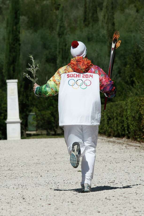 First torchbearer Yiannis Antoniou from Greece runs to the monument of Pierre de Coubertin during the torch relay after the ceremony of lighting of the Olympic flame at Ancient Olympia, in west southern Greece on Sunday  Sept. 29, 2013. The flame will be transported by torch relay to the Russian resort of Sochi, which will host the Feb. 7-23, 2014 Winter Olympics. (AP Photo (AP Photo/Dimitri Messinis/pool) ORG XMIT: AOLY118 Photo: Dimitri Messinis / AP POOL