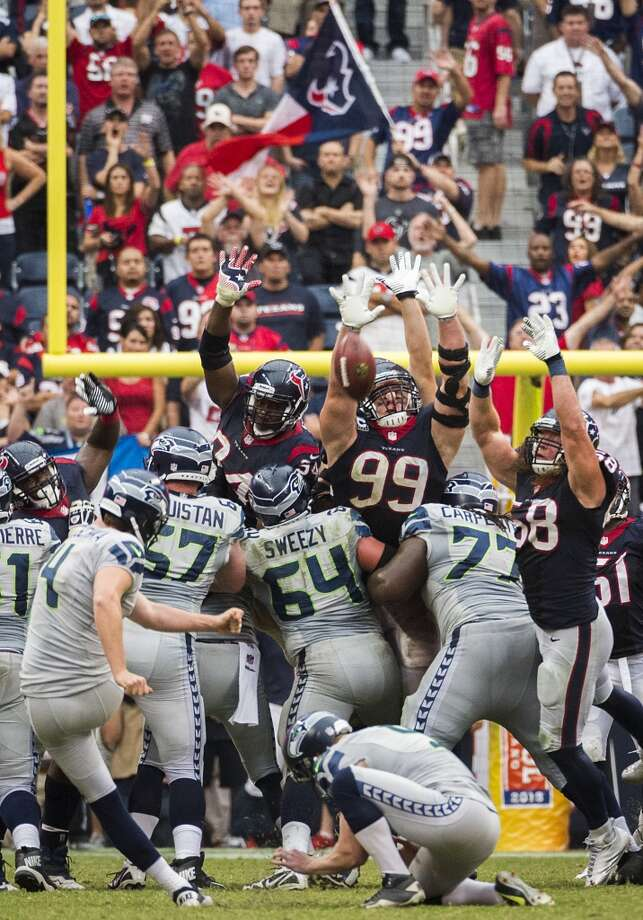 Seahawks kicker Steven Hauschka (4) kicks a 45-yard game-winning field goal over the outstretched hands of Texans defensive end Antonio Smith (94), defensive end J.J. Watt (99) and outside linebacker Brooks Reed (58). Photo: Smiley N. Pool, Houston Chronicle