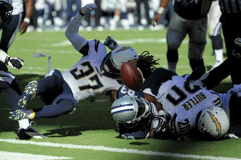 Jahleel Addae (left) and Crezdon Butler of the Chargers force a fumble by Cowboys receiver Terrance Williams at San Diego's 1-yard line in the final moments. Photo: Denis Poroy / Associated Press