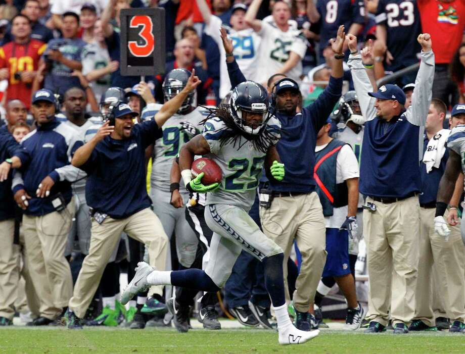 At least one member of the Seahawks' sideline contingent correctly predicts the result of cornerback Richard Sherman's interception return. Photo: Cody Duty, Staff / © 2013 Houston Chronicle