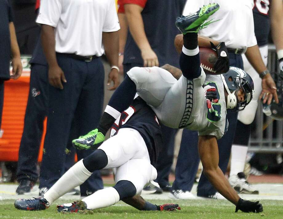 Texans cornerback Kareem Jackson, bottom, slams Seahawks receiver Doug Baldwin to the turf, drawing a big personal foul in Seattle's game-winning drive. Photo: Brett Coomer, Staff / © 2013  Houston Chronicle