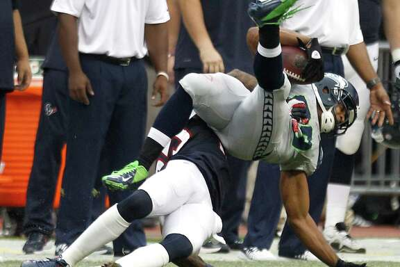 Texans cornerback Kareem Jackson, bottom, slams Seahawks receiver Doug Baldwin to the turf, drawing a big personal foul in Seattle's game-winning drive.