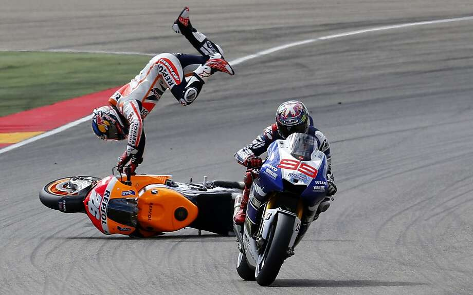 TOPSHOTS-Repsol Honda Team's Spanish rider Dani Pedrosa (L) falls behind Yamaha Factory Racing's Spanish rider Jorge Lorenzo during the MotoGP race of the Aragon Grand Prix at the Motorland racetrack in Alcaniz on September 29, 2013.   AFP PHOTO / JOSE JORDANJOSE JORDAN/AFP/Getty Images Photo: Jose Jordan, AFP/Getty Images
