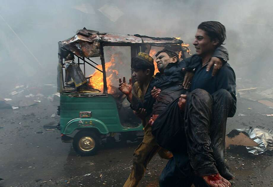 TOPSHOTS-Pakistani men carry an injured blast victim at the site of a bomb explosion in the busy Kissa Khwani market in Peshawar on September 29, 2013. A bomb explosion killed at least 31 people in Pakistan's northwestern city of Peshawar, officials said -- the third deadly strike to hit the city in the last week.  AFP PHOTO / HASHAM AHMEDHASHAM AHMED/AFP/Getty Images Photo: Hasham Ahmed, AFP/Getty Images