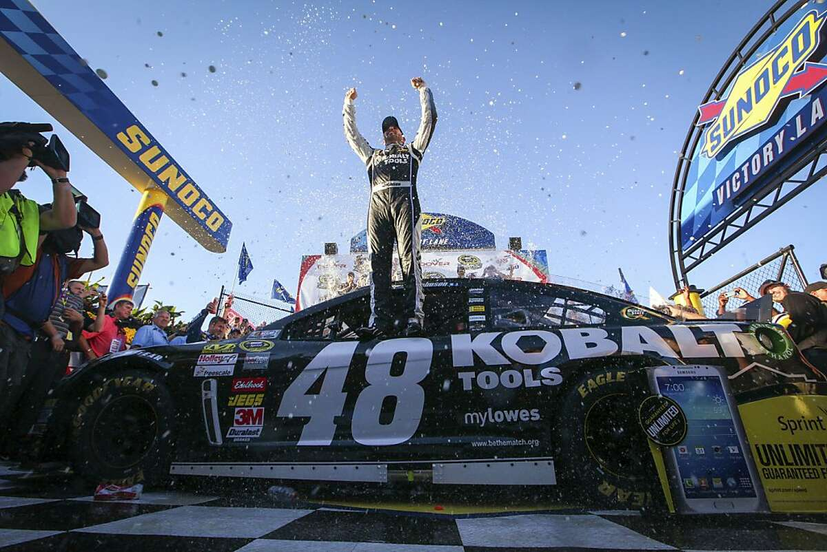 Jimmie Johnson celebrates in Victory Lane after winning the NASCAR Sprint Cup Series auto race Sunday, Sept. 29, 2013, in Dover, Del. (AP Photo/The News-Journal, Suchat Pederson) NO SALES