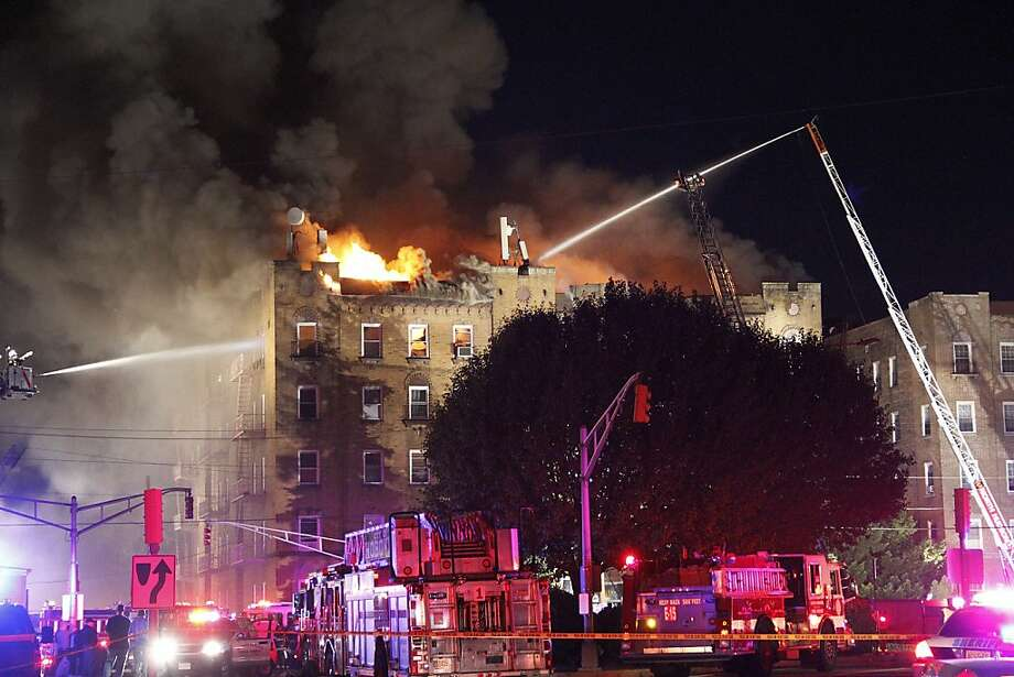 A fire erupted on the top floor of an apartment building in North Bergen, N.J., on 92nd Street and Kennedy Blvd, emergency vehicles were on the scene trying to tame the fire, Sunday, Sept. 29, 2013. (AP Photo/The Jersey Journal, Ashlee Espinal) Photo: Ashlee Espinal, Associated Press