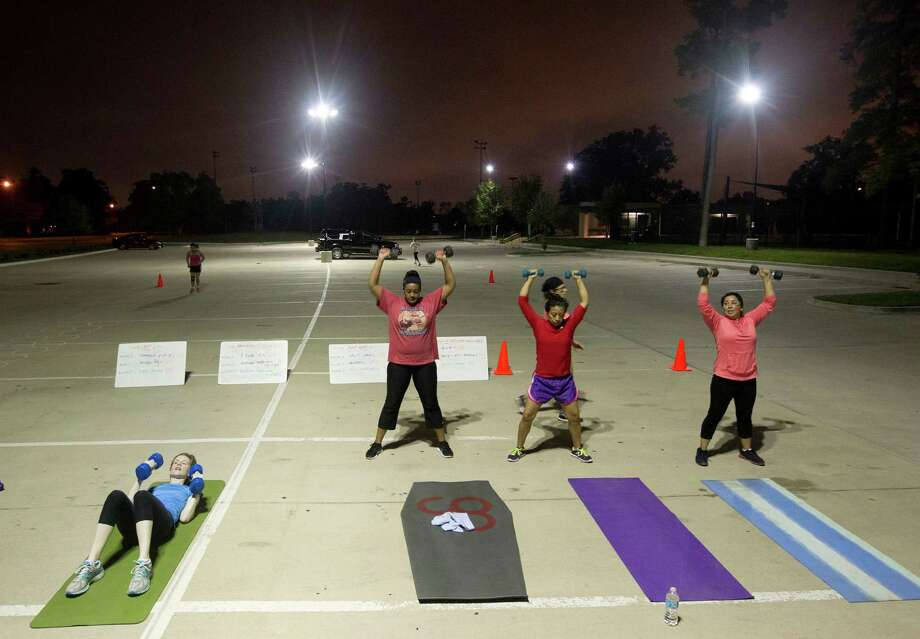 Before sunrise a group of about 10 people workout in a parking lot during a Camp Gladiator fitness boot camp at T.C. Jester Park Monday, Sept. 30, 2013, in Houston. Photo: Johnny Hanson, Houston Chronicle / Houston Chronicle