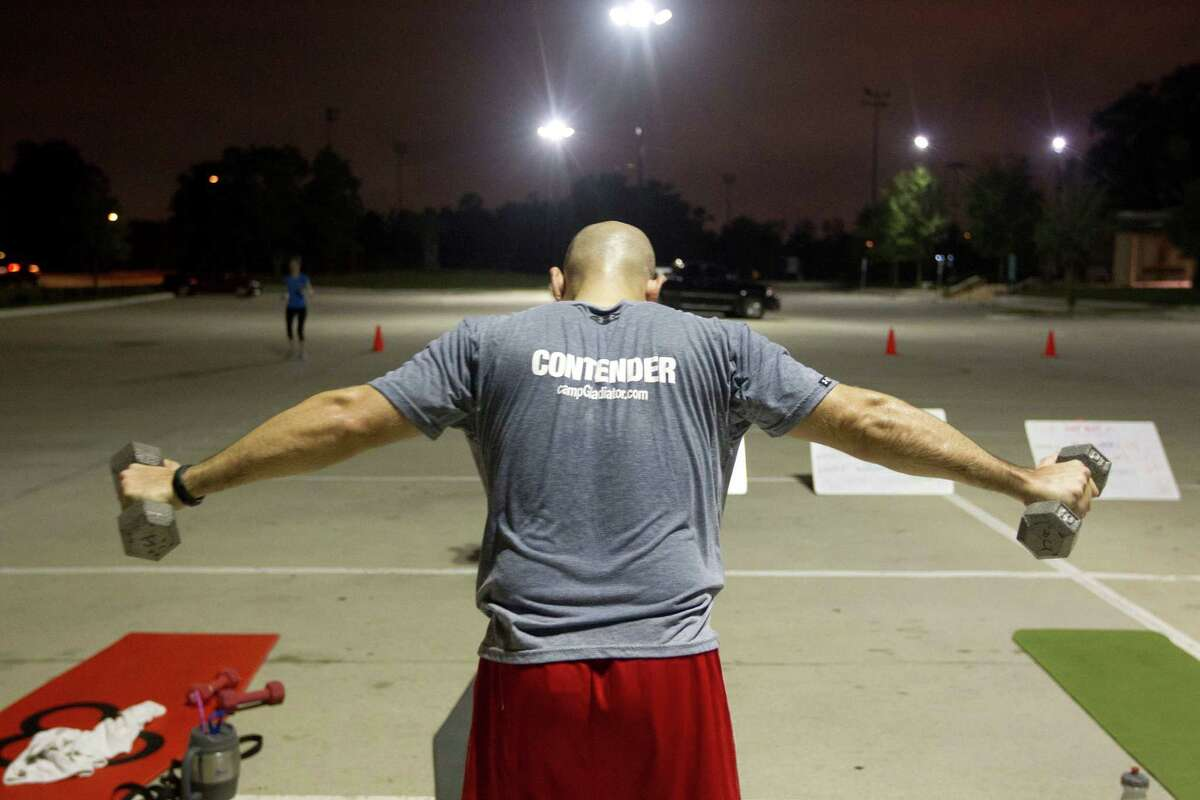 John Augusto, 33, lifts dumbbells during an early morning Camp Gladiator fitness boot camp at T.C. Jester Park Monday, Sept. 30, 2013, in Houston.