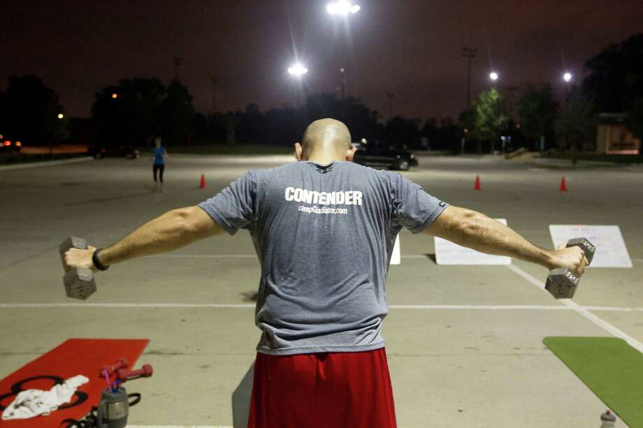 John Augusto, 33, lifts dumbbells during an early morning  Camp Gladiator fitness boot camp at T.C. Jester Park Monday, Sept. 30, 2013, in Houston. Photo: Johnny Hanson, Houston Chronicle / Houston Chronicle