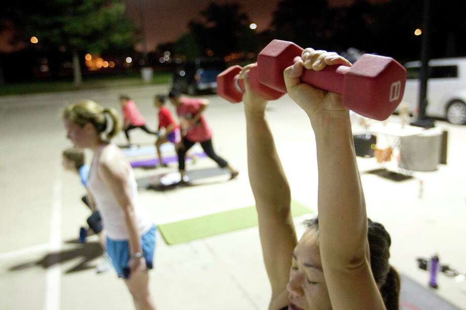 Hien Reynoso, 39, lifts dumbbells during an early morning Camp Gladiator fitness boot camp at T.C. Jester Park Monday, Sept. 30, 2013, in Houston. Photo: Johnny Hanson, Houston Chronicle / Houston Chronicle