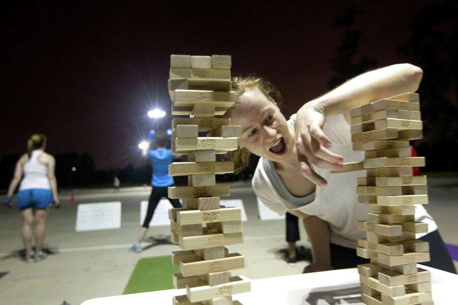 "Making the work outs a bit more competitive and fun, Emily Paloski, 32, attempts to remove a Jenga game piece during her early morning workout at the Camp Gladiator fitness boot camp at T.C. Jester Park Monday, Sept. 30, 2013, in Houston. ""We add games to make the workouts more fun,"" instructor Renee Rivellini said. Photo: Johnny Hanson, Houston Chronicle / Houston Chronicle"