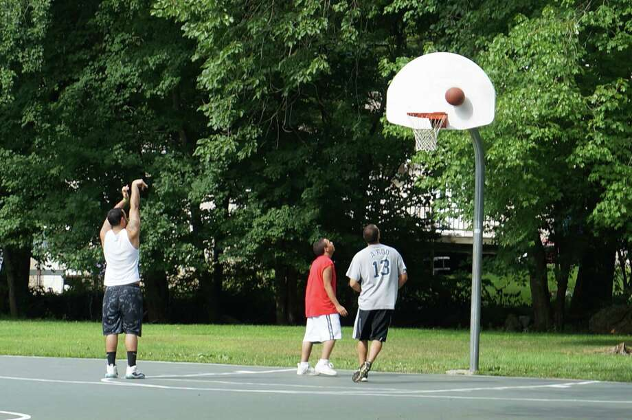 "Young men playing basketball at Highwood Park one afternoon in late August. A ""gangsta"" invasion or just some guys playing pickup games after work? Photo: Genevieve Reilly / Fairfield Citizen"