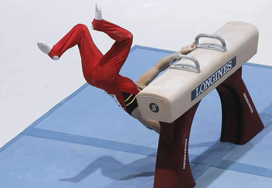 Thrown by the pommel horse,Daan Kenis of Belgium spills to the mat during a qualification round for the 