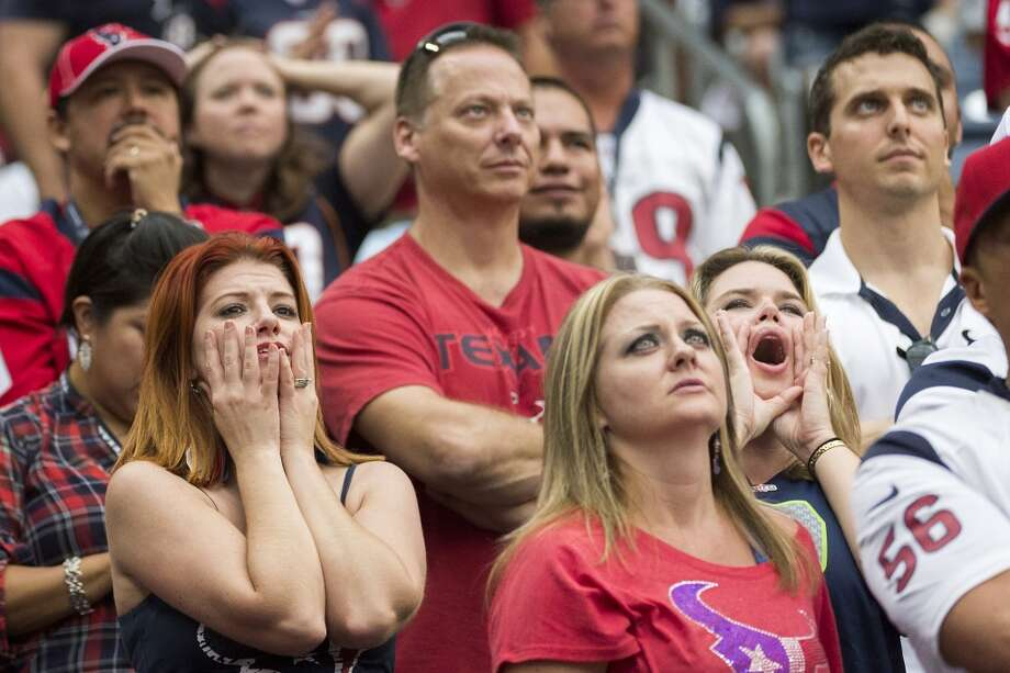 Texans fans react after Seahawks cornerback Richard Sherman returned a Matt Schaub interception for a touchdown during the second half. Photo: Smiley N. Pool, Houston Chronicle