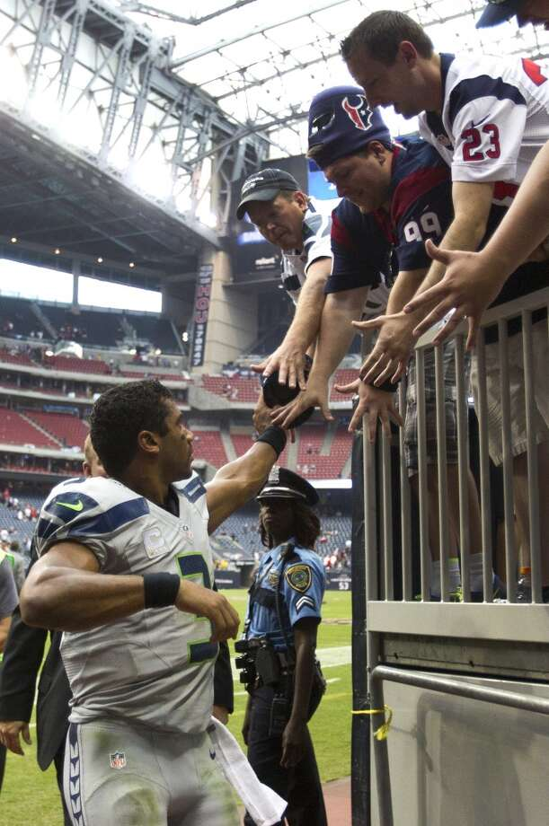 Seahawks quarterback Russell Wilson slaps hands with fans as he leaves the field after the Seahawks beat the Texans in overtime. Photo: Brett Coomer, Houston Chronicle