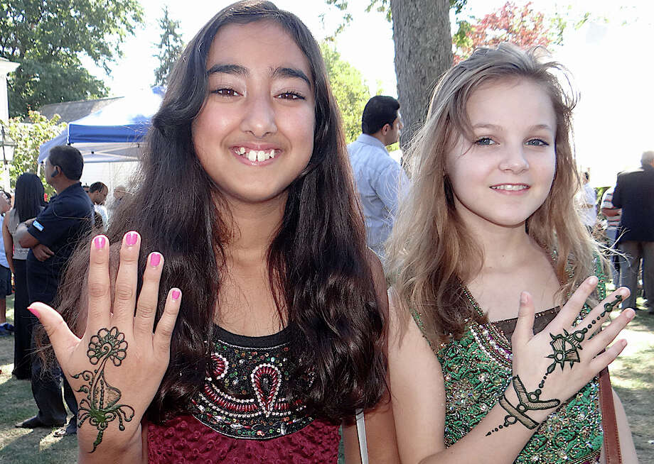 Ria Narula and Juliet Nannariello, both 11, show off new henna tattoos at the 7th annual Heritage India Festival Sunday on Town Hall Green. Photo: Mike Lauterborn / Fairfield Citizen contributed