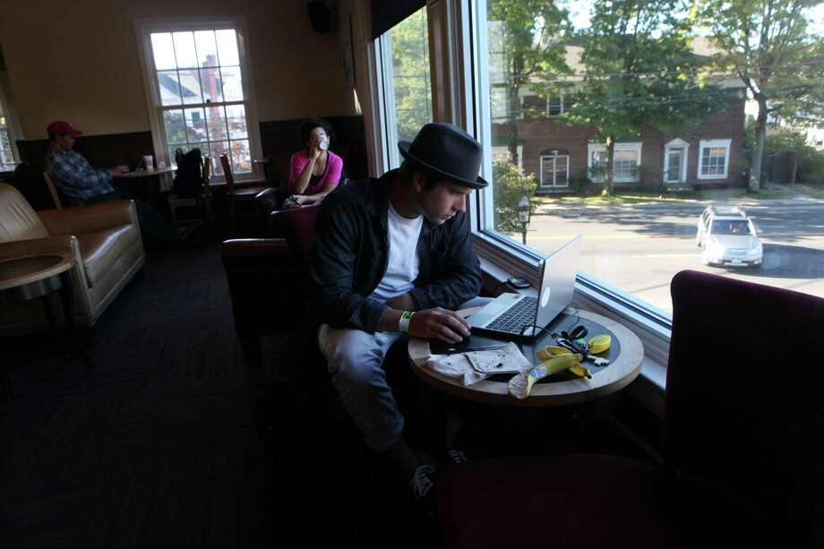 Commuter Ian Knowles, of Fairfield, decides to work from Starbucks in downtown Fairfield instead of taking the train to Manhattan on Monday, Sept. 30, 2013. TheMetro North trains were running on 50 percent capacity after last weeks electrical failure. Photo: BK Angeletti, B.K. Angeletti / Connecticut Post freelance B.K. Angeletti
