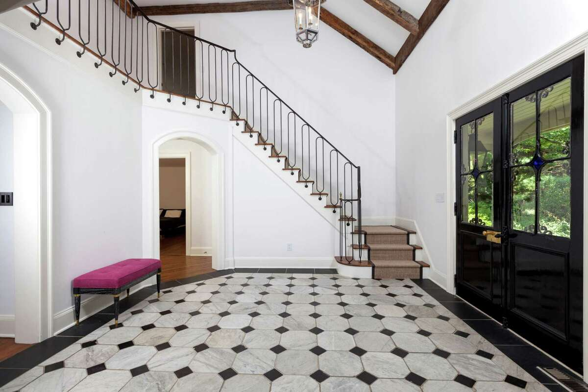 Once inside 90 Parade Hill Lane in New Canaan is a tiled hall with twin chandeliers, stairs that sweep up to a nearby balcony and a vaulted ceiling with wood beams.