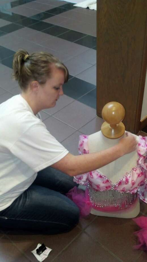 Katy Edgar, program intake coordinator at Gift of Life, readies bra for display at the Artusd of Southeast Texas.