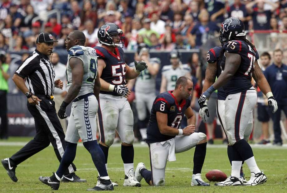 Matt Schaub climbs to his feet after losing his helmet on a sack from Seahawks defensive end Cliff Avril during the fourth quarter. Photo: Cody Duty, Houston Chronicle