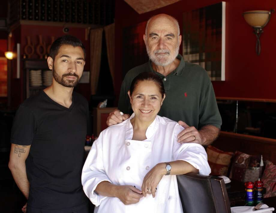 L to R: Berk Guvenc, left, his mom and chef, Meral, and her husband, Celal Alpay are seen in their San Francisco restaurant, Tuba. Photo: Russell Yip, The Chronicle