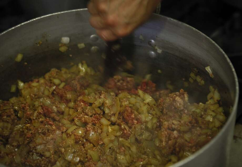 Meral Guvenc sautes the meat, onions and spices for Icli Kofte. Photo: Russell Yip, The Chronicle