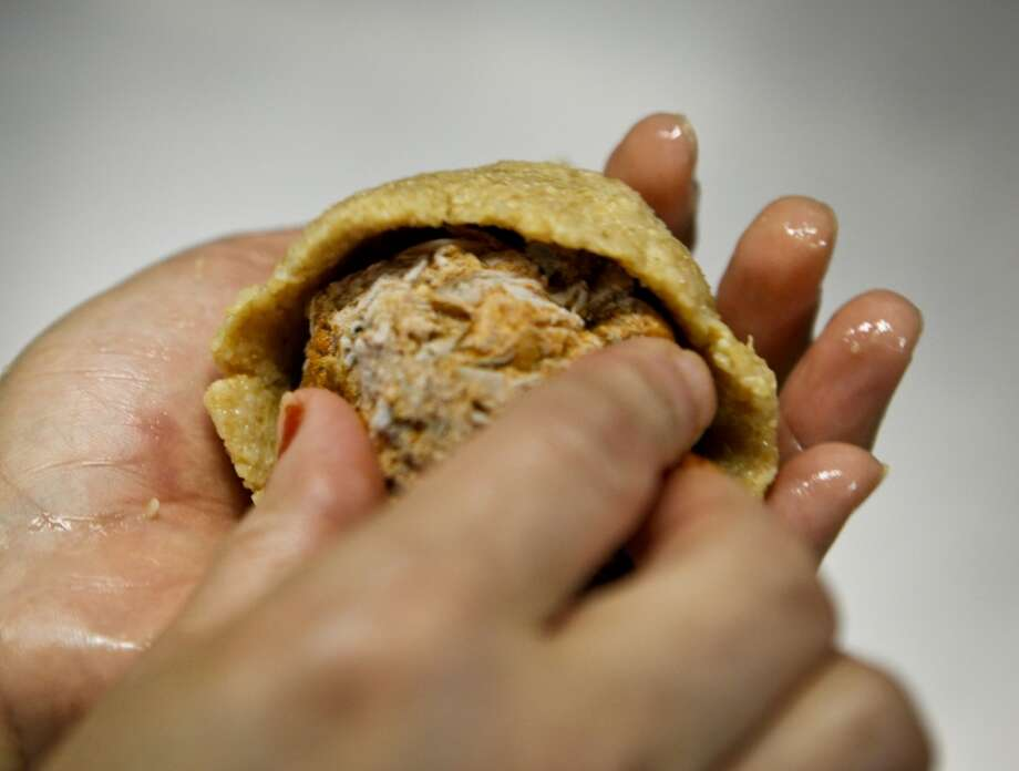 Meral Guvenc puts a meatball in a bulgar shell to make Icli Kofte. Photo: Russell Yip, The Chronicle