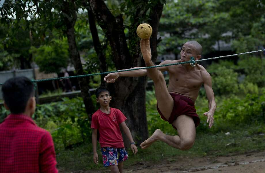 Let's see Misty May-Treanor do this:A Buddhist monk leaps to kick a rattan ball over a rope during a game of Chinlone 