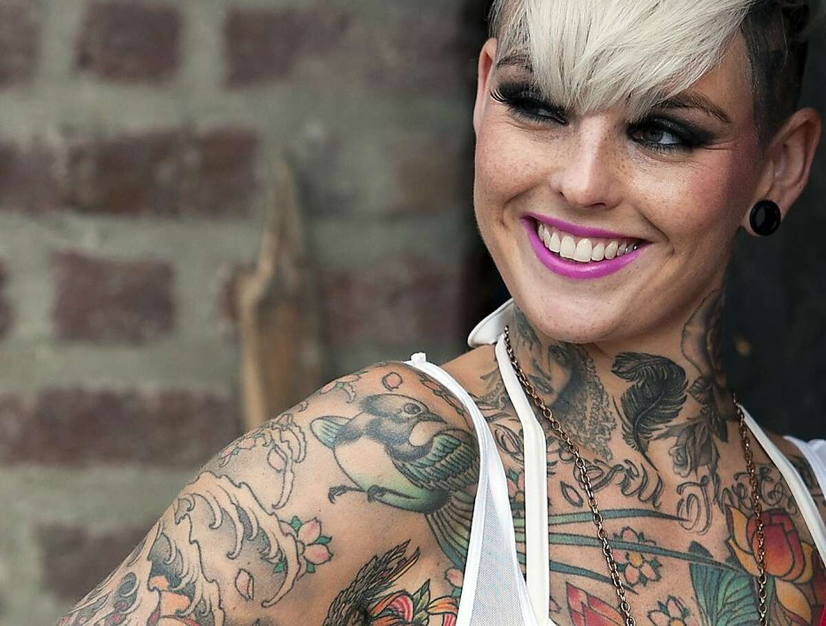 Art collector: A well-inked Briton is happy to show off her illustrations at the London Tattoo Convention.
