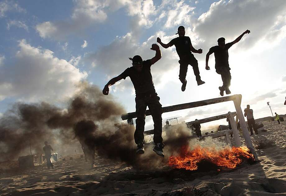 Graduation day:Palestinian militants of the Al-Nasser Brigades, the armed wing of the Popular Resistance Committees,   leap over a flaming obstacle during a graduation ceremony in Khan Younis, Gaza Strip. Photo: Said Khatib, AFP/Getty Images