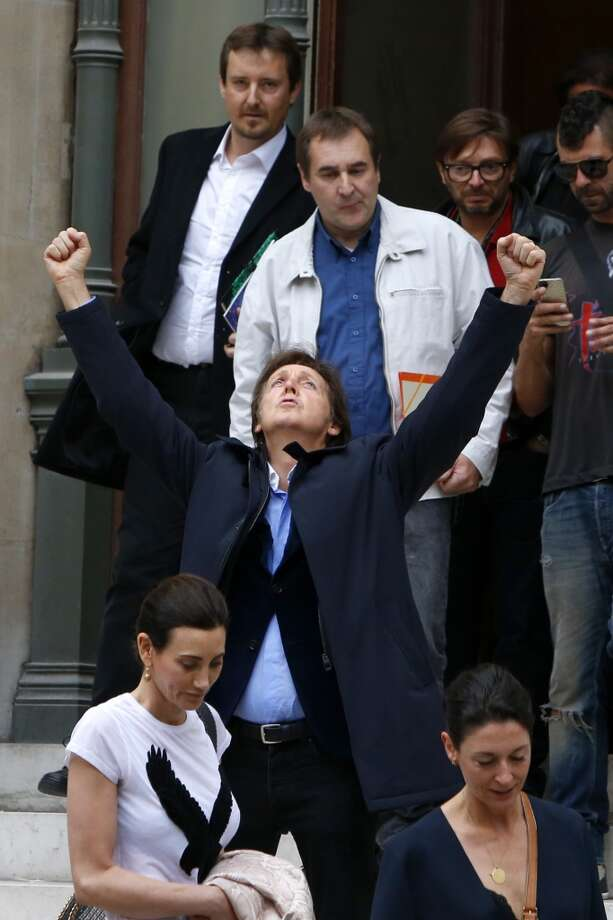Sir Paul McCartney, centre, gestures for photographers as he exits the Opera House after attending the presentation of his daughter Stella McCartney's ready-to-wear Spring/Summer 2014 fashion collection, Monday, Sept. 30, 2013 in Paris. Photo: Francois Mori, Associated Press