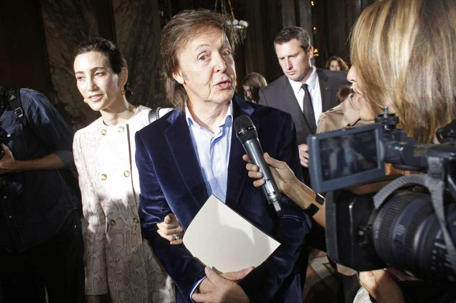 Sir Paul McCartney, centre, answers a reporter's questions as he leaves, along with Nancy Shevell, left, after attending the presentation of Stella McCartney's ready-to-wear Spring/Summer 2014 fashion collection, Monday, Sept. 30. Photo: Thibault Camus, Associated Press